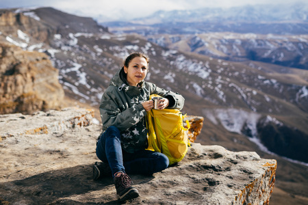 Active young girl sits on the edge of the mountain, with a yellow backpack, enjoys the mountain nature and the sun