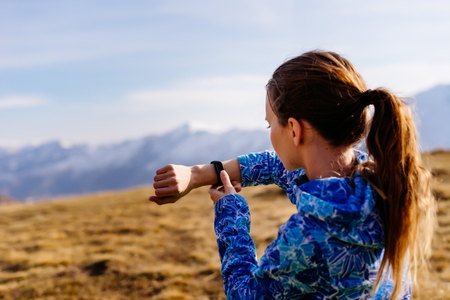 cute young girl in a blue jacket travels through the Caucasus mountains, watches time on a wristwatch
