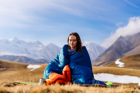 cute young girl in a blue sleeping bag sits on the background of the Caucasian ridge, enjoys nature
