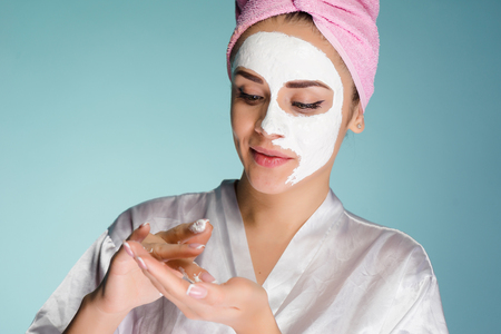 cute young girl with a pink towel on her head applying a white moisturizing mask on her face