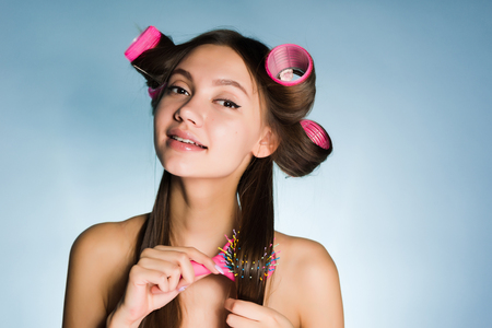 beautiful young girl makes a fashionable hairstyle with a comb and hair curlers