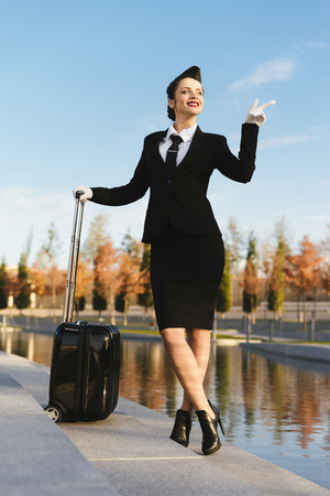 confident beautiful stewardess girl in uniform, with a suitcase, thinking about the sky