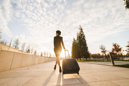 Woman stewardess is carrying a big black suitcase