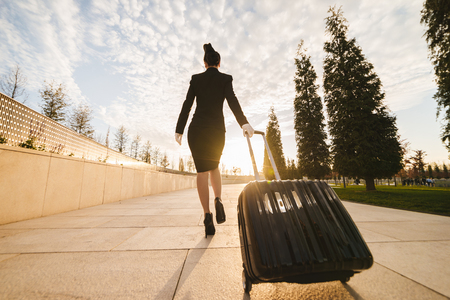 A female flight attendant in the form carries a large suitcase 版權商用圖片