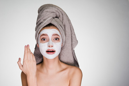 woman with a towel on her head applied a white mask to her face