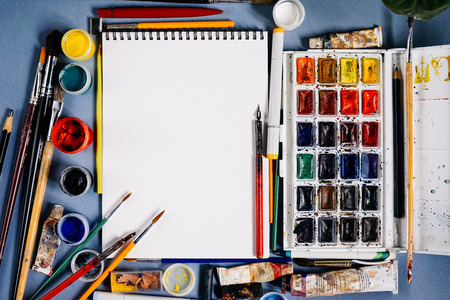 Designer notebook on a background of multi-colored paints