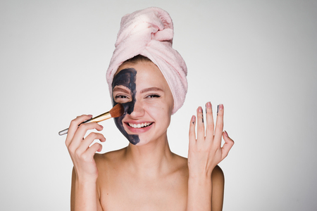happy woman with a towel on her head puts on face mask Stock Photo