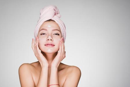 mujer con toalla en su cabeza después de la crema