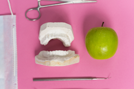 on a pink background lie a cast of teeth, an apple