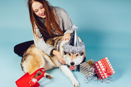 happy woman in holiday hat stroking dog on gift background