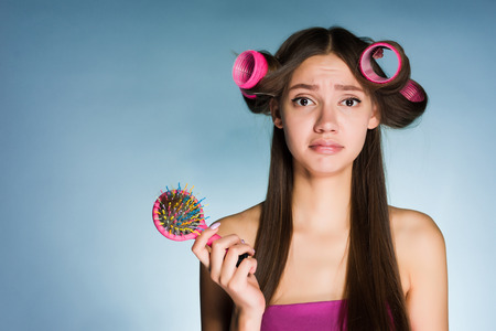 a frustrated girl with curlers on her head on a blue background