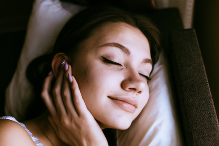 woman sleeps on the bed and inserts headphones into her ears Stock Photo