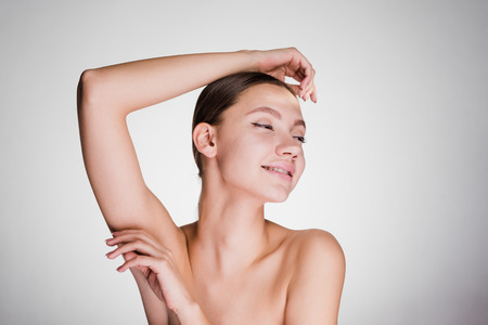 happy woman looks after armpits on a gray background Stock Photo