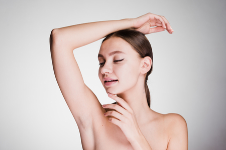 a surprised woman on a gray background shows her armpits