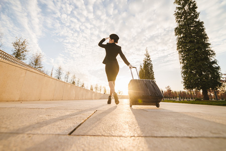 woman in flight stewardess carries a suitcase
