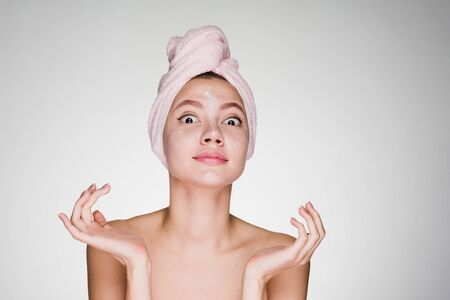 the amazed woman with a towel on her head after shower applied cream on her face