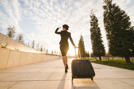 woman in flight stewardess carries a large suitcase