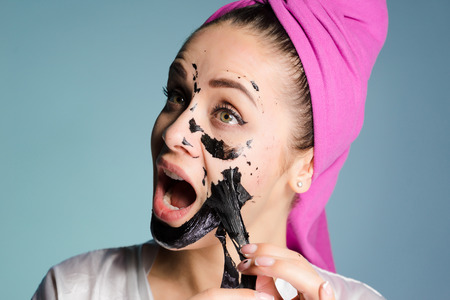 funny young girl with a pink towel on her head removes the black mask from her face