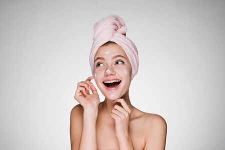 happy woman with a towel on her head apply cream on face skin