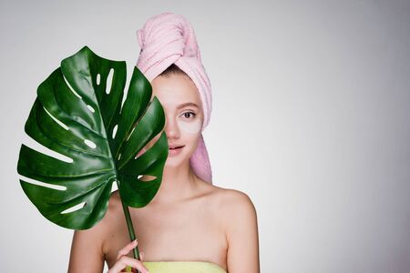 a dazed woman with a towel on her head after the shower put patches under her eyes Stock Photo