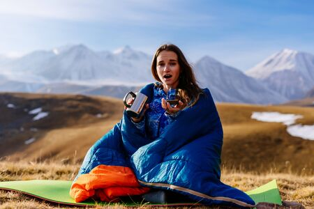 a woman is sitting in a sleeping bag having just woken up in a hike