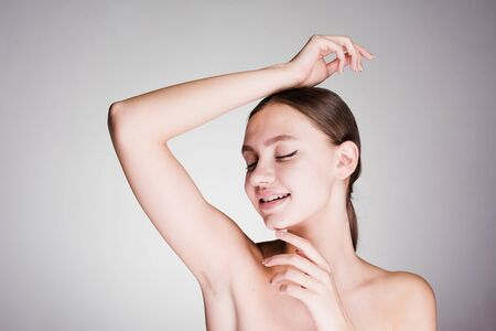 astonished woman cares for the underarm skin on a gray background