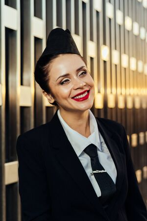 happy woman stewardess in uniform posing at camera