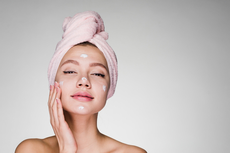 Woman with towel on her head after showering cream on face