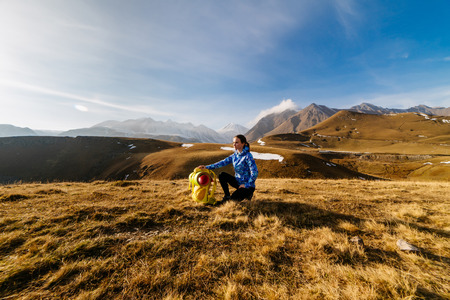 a young girl in a blue jacket travels along the Caucasian ridge, enjoys nature and clean air Stock Photo