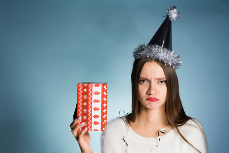 the sad young girl is dissatisfied with a New Years gift, on a head a festive cap, is angry
