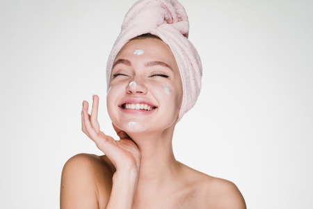 happy woman with a towel on her head apply cream on her face