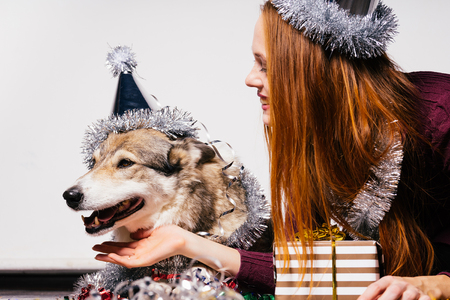 happy woman in a festive hat stroking a dog