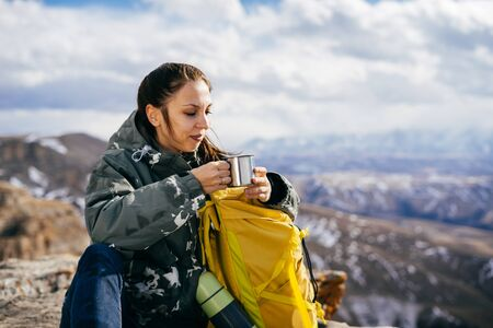 woman tourist drinks hot tea on the background of mountains on a sunny day