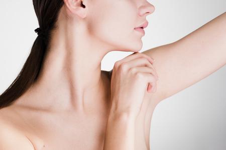 een vrouw zorgt voor de oksels op een grijze achtergrond Stockfoto