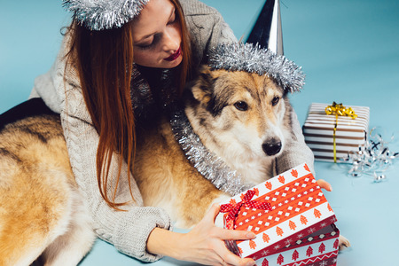 woman in a festive hat hugs a big dog and opens a gift