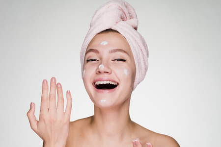 happy woman after shower puts cream on face Stock Photo