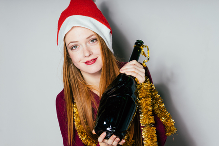 woman in a New Year hat holds a bottle in hands