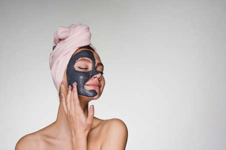 a surprised woman with a towel on her head applied a mask to her face Stock Photo