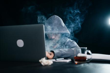 mysterious man hides his face under the hood, smokes hookah, lots of smoke, hacks laptop