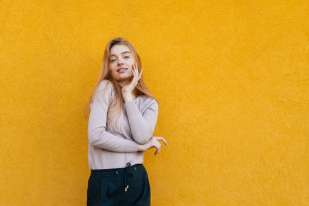 beautiful attractive blond girl in stylish clothes posing on yellow background