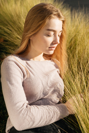 young beautiful blond girl lies on a meadow, enjoys the sun, eyes are closed Stock Photo