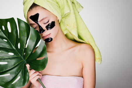 young girl with a green towel on her head enjoying a spa, under the eyes of black patches, holds a green leaf Stock Photo