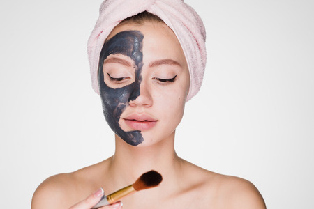 cute young girl with a pink towel on her head puts on face clay mask Stock Photo