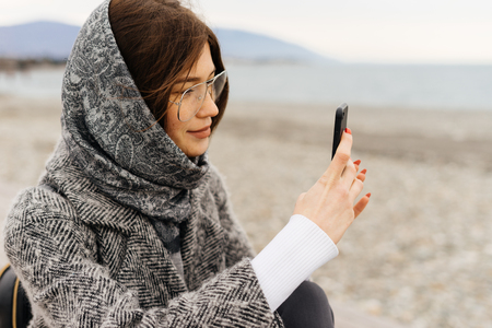 stylish young girl with a gray scarf and glasses takes pictures of a beautiful street Stock Photo