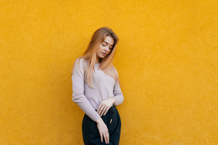stylish slender girl blonde in a white jacket posing against a yellow wall Stock Photo