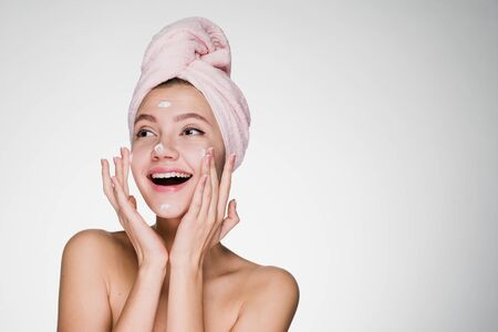 happy young girl with pink towel on head applying moisturizer on face