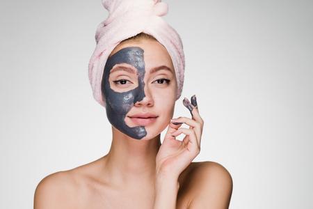 그녀의 머리에 분홍색 수건으로 젊은 매력적인 여자는 절반 얼굴에 유용한 클레이 마스크를 적용