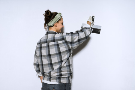 cute young girl in a plaid shirt doing repairs in her apartment, leveling the walls with a spatula