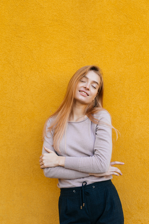 young beautiful blonde girl posing on yellow wall background, smiling, street style