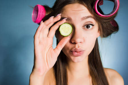 cute young girl wants to look good, on the head of the curler, keeps the cucumber for moisturizing the skin of the face
